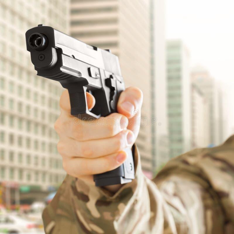 Hombre en la ciudad que sostiene el arma en su mano imágenes de archivo libres de regalías