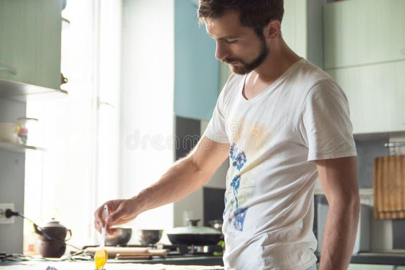 Hombre en la cocina con un cepillo culinario imágenes de archivo libres de regalías