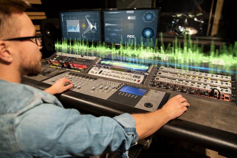 Hombre en la consola de mezcla en el estudio de grabación de la música imagen de archivo