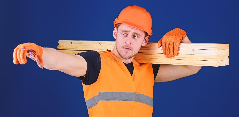 Hombre en la direcci?n punteaguda del casco, del casco y de los guantes protectores, fondo azul Concepto de madera de los materia fotografía de archivo libre de regalías