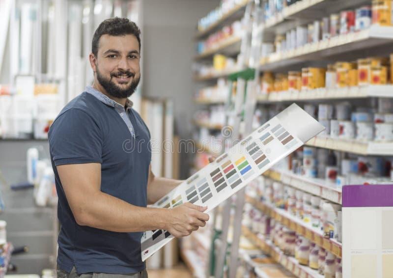 Hombre en la droguería que selecciona el color de la pintura para su trabajo fotografía de archivo libre de regalías