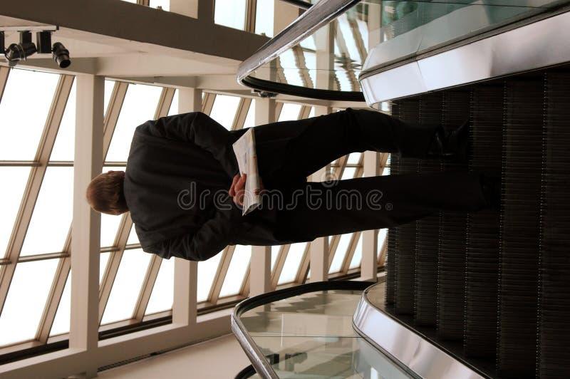 Hombre en la escalera móvil fotos de archivo