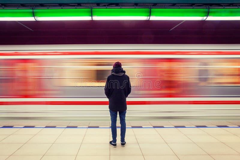 Hombre en la estación de metro y el tren móvil foto de archivo