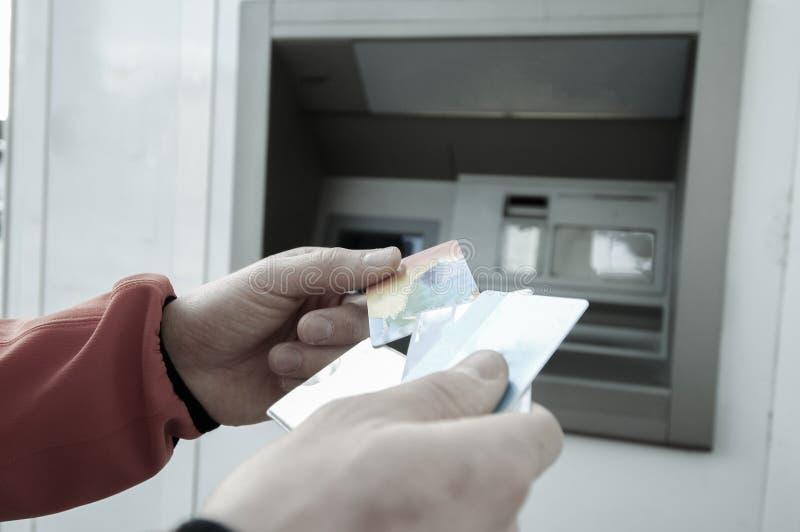 Hombre en la máquina de la atmósfera con el escondite del crédito y de las tarjetas de débito imágenes de archivo libres de regalías