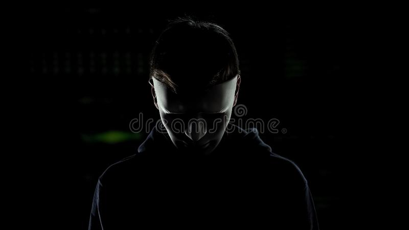 Hombre en la máscara asustadiza aislada en el fondo oscuro, identidad de ocultación del asesino en serie imagenes de archivo