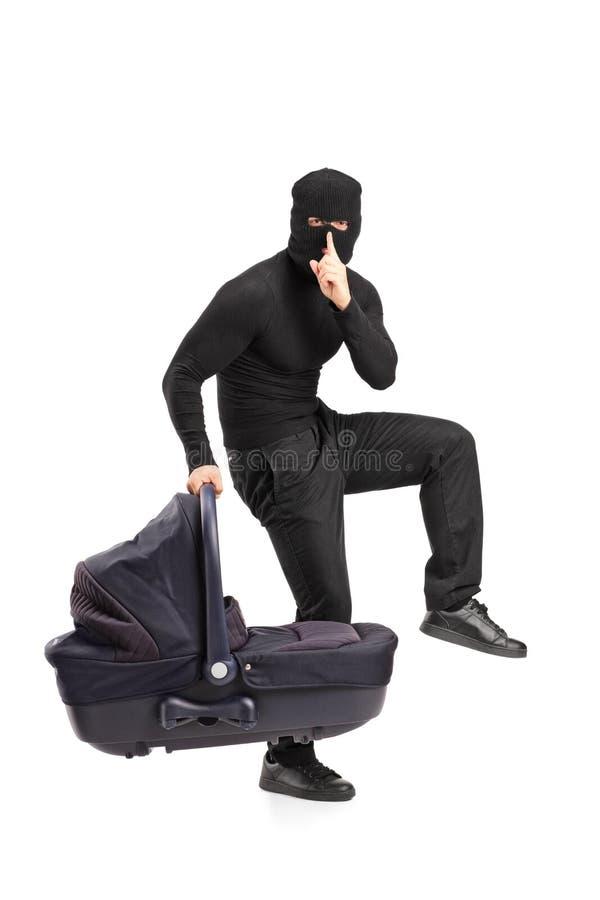 Hombre en la máscara del robo que lleva a cabo un carrycot imagenes de archivo
