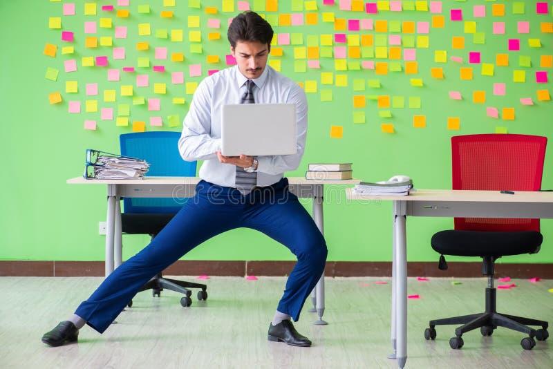Hombre en la oficina con muchas prioridades en conflicto que hacen exercis imagenes de archivo