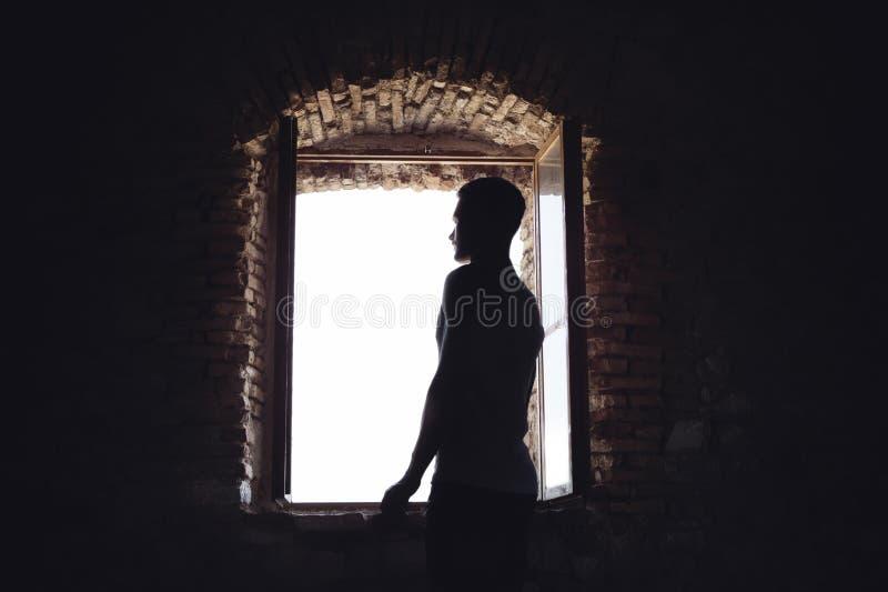 Hombre en la oscuridad aclarada por el sol de una ventana imágenes de archivo libres de regalías