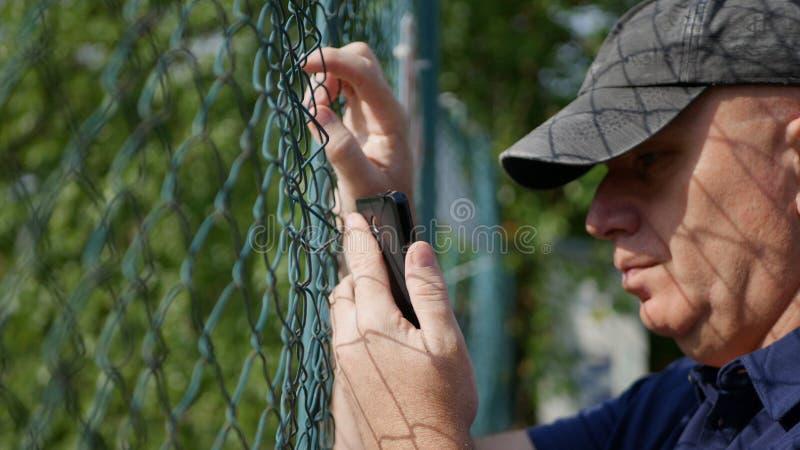 Hombre en la parte de atrás de una cerca metálica Reading un texto usando Smartphone imágenes de archivo libres de regalías