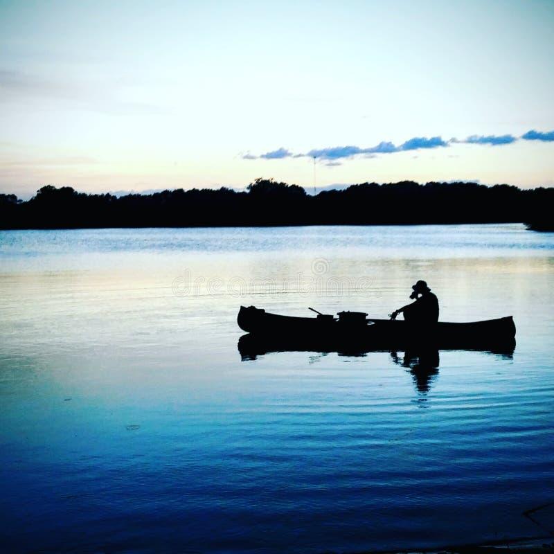 Hombre en la pesca de la canoa en el lago foto de archivo
