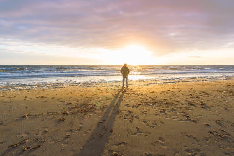 Hombre en la playa que mira las ondas imágenes de archivo libres de regalías