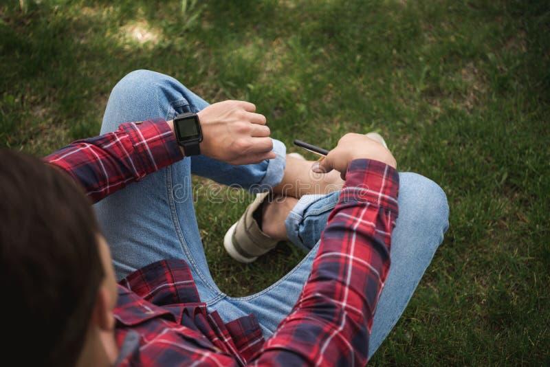 Hombre en la ropa casual que mira el reloj y que espera alguien en el parque imágenes de archivo libres de regalías