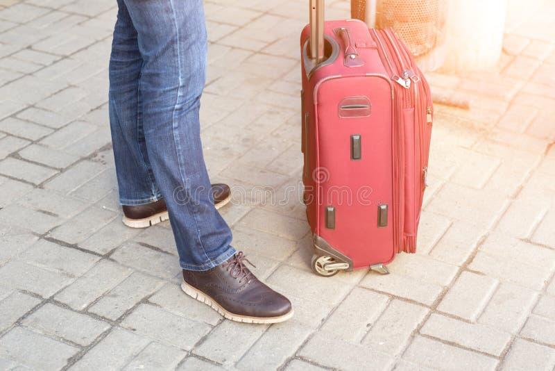 Hombre en la ropa casual que se coloca con la maleta roja en la estación Viaje dealyed que espera del viajero moderno joven para  fotografía de archivo libre de regalías