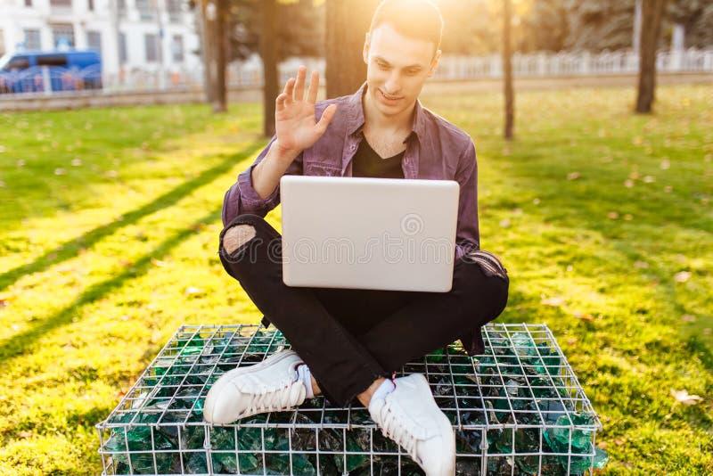 Hombre, en la ropa casual, sentándose en un banco, con un ordenador portátil, talki fotos de archivo libres de regalías