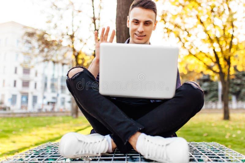 Hombre, en la ropa casual, sentándose en un banco, con un ordenador portátil, talki foto de archivo libre de regalías