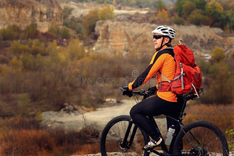 Hombre en la ropa de deportes que salta arriba en la bicicleta de la montaña en el fondo del paisaje imágenes de archivo libres de regalías
