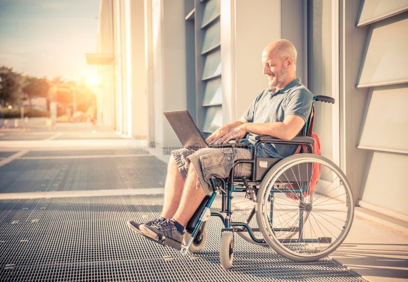 Hombre en la silla de rueda usando el ordenador fotos de archivo libres de regalías
