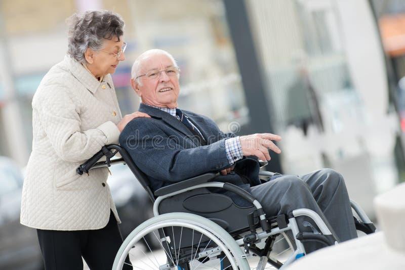 Hombre en la silla de ruedas con la esposa optimista al aire libre foto de archivo libre de regalías