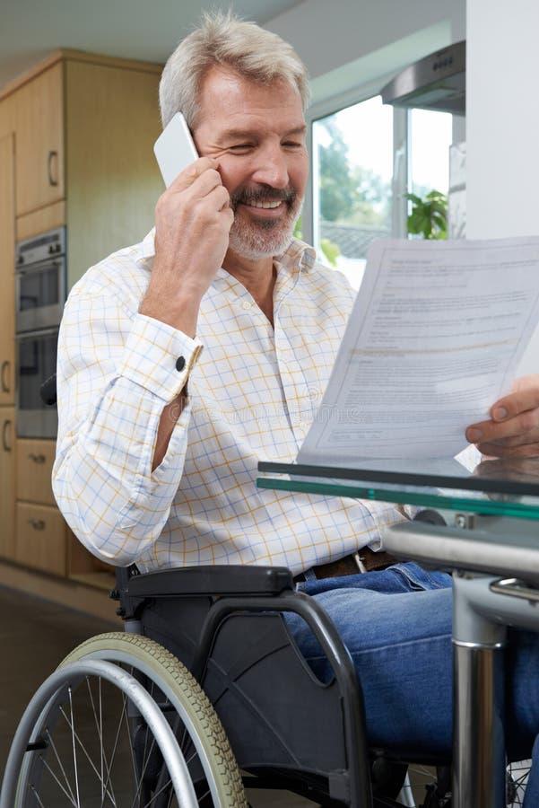 Hombre en la silla de ruedas que hace llamada de teléfono mientras que lee la letra fotos de archivo