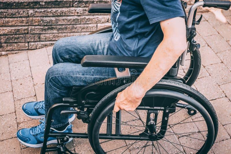 Hombre en la silla de ruedas que lleva a cabo las manos en la rueda fotografía de archivo