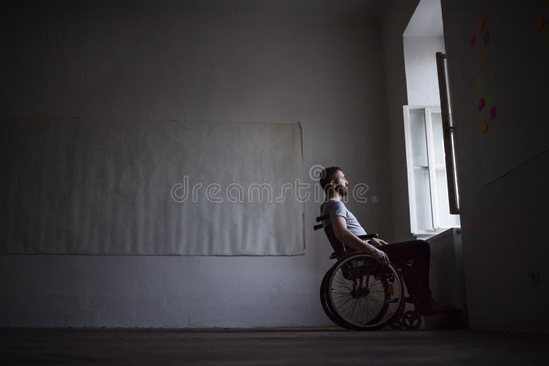 Hombre en la silla de ruedas que mira fuera de la ventana fotos de archivo