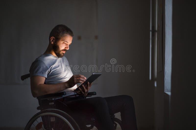 Hombre en la silla de ruedas que trabaja con la tableta imágenes de archivo libres de regalías