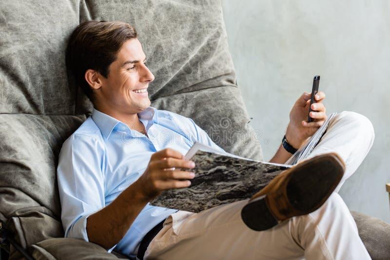 Hombre en la silla que manda un SMS con el teléfono móvil imagen de archivo