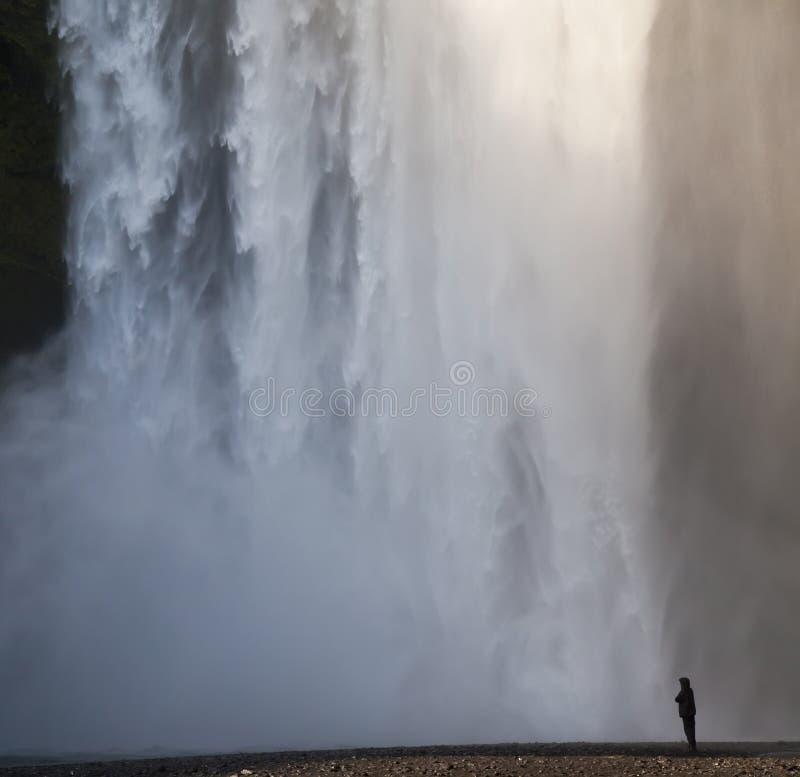 Hombre en la situación negra en una cascada fotografía de archivo