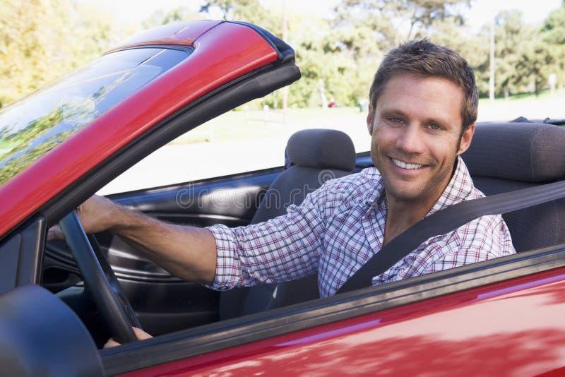 Hombre en la sonrisa convertible del coche foto de archivo libre de regalías