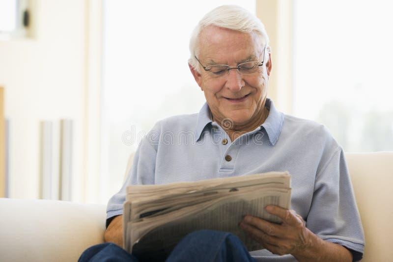 Hombre en la sonrisa del periódico de la lectura de la sala de estar imágenes de archivo libres de regalías