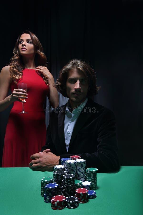Hombre en la tabla de la ruleta rodeada por las mujeres hermosas fotos de archivo libres de regalías