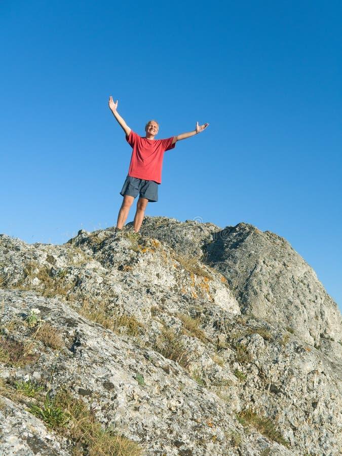 Hombre en la tapa de la montaña imagen de archivo