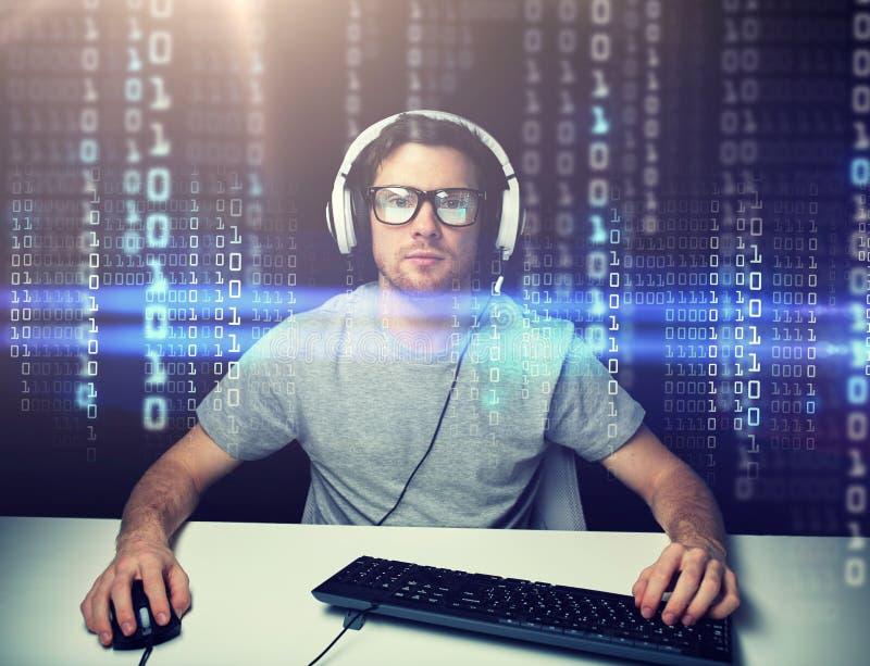 Hombre en las auriculares que cortan el ordenador o la programación fotos de archivo