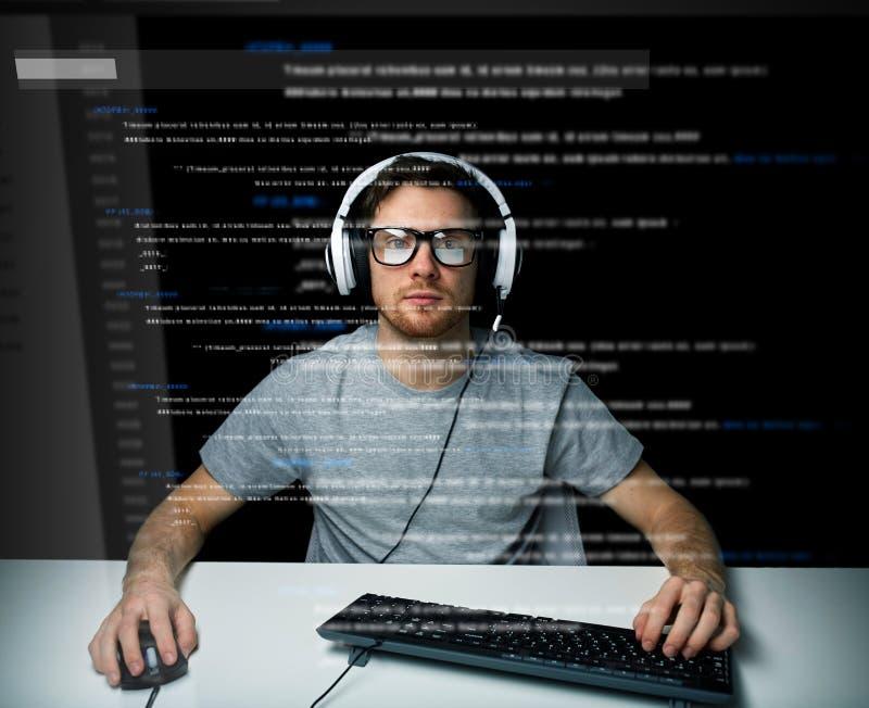 Hombre en las auriculares que cortan el ordenador o la programación imagen de archivo libre de regalías