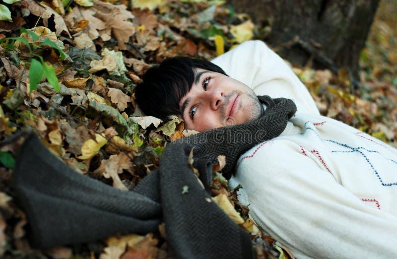 Hombre en las hojas de otoño imagenes de archivo