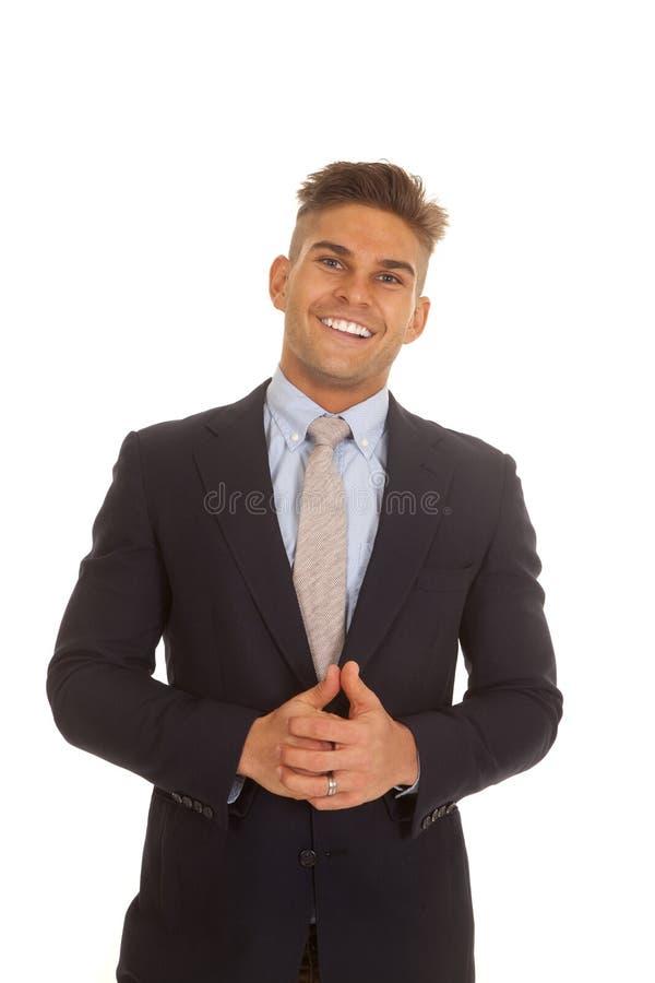 Hombre en las manos de la sonrisa de la capa del traje abrochadas imagen de archivo libre de regalías