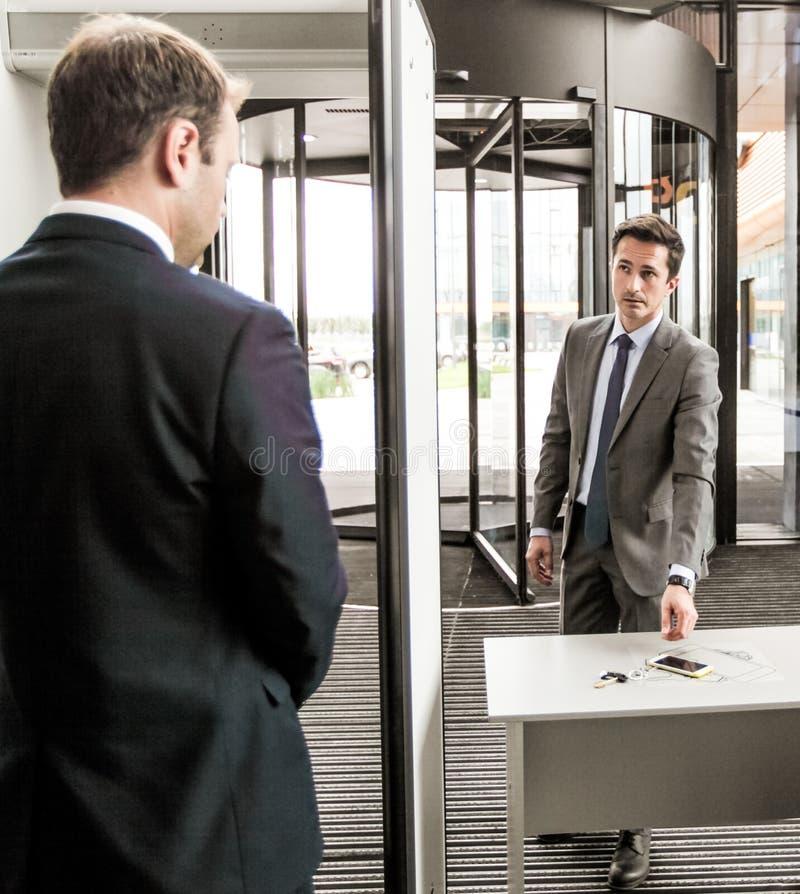 Hombre en las puertas de seguridad aeroportuaria fotografía de archivo libre de regalías