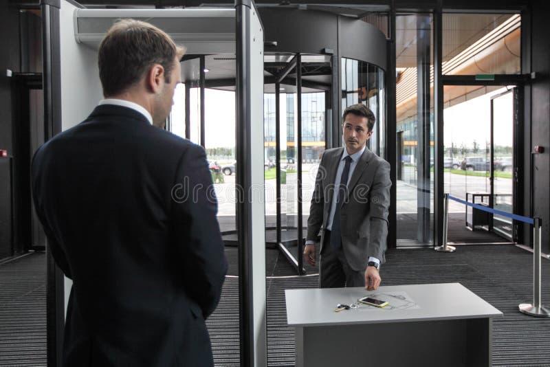 Hombre en las puertas de seguridad aeroportuaria imágenes de archivo libres de regalías