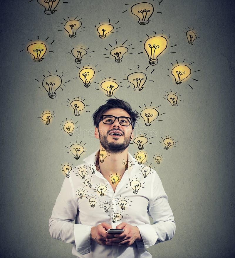 Hombre en lentes con smarpthone produciendo el un montón de ideas acertadas fotografía de archivo libre de regalías