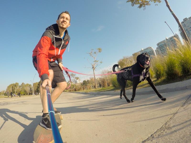 Hombre en longboard con el perro foto de archivo