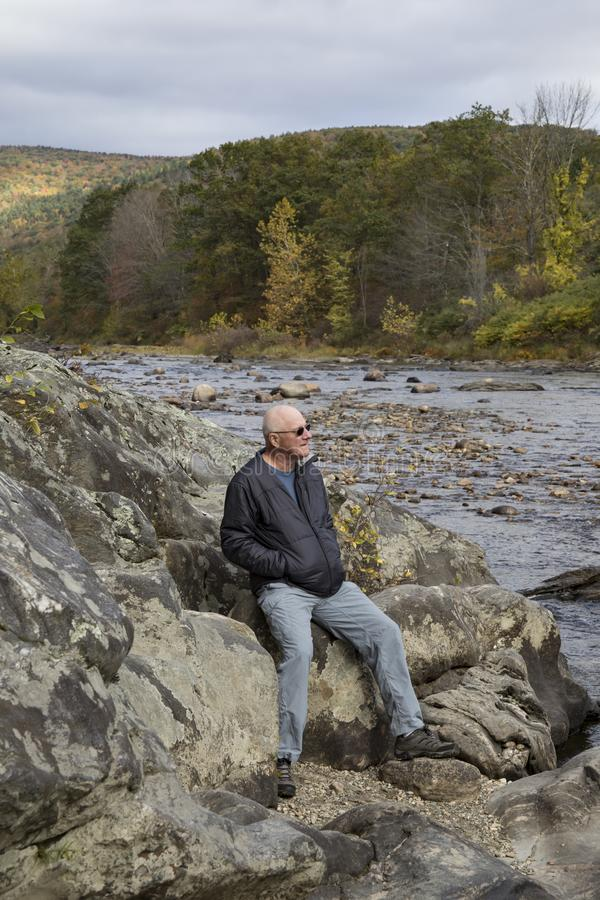 Hombre en los bancos rocosos del campo rural de Vermont imagen de archivo libre de regalías