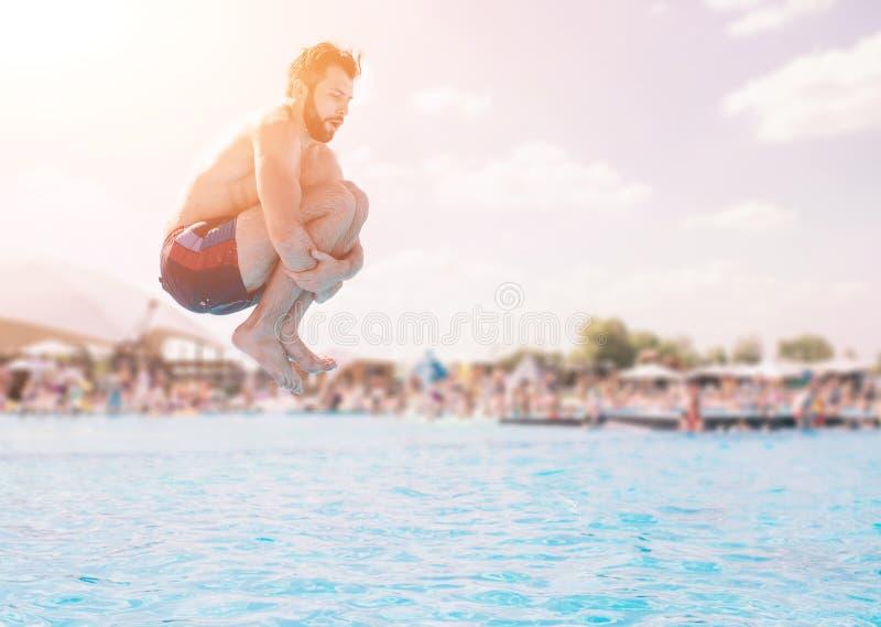 Hombre en los pantalones cortos azules y rojos que saltan en piscina en el día soleado Disfrutar de la fiesta en la piscina con l imagen de archivo
