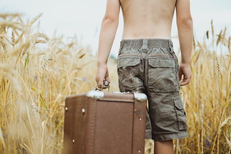 Hombre en los pantalones cortos que sostienen la maleta retra en campo de fotos de archivo