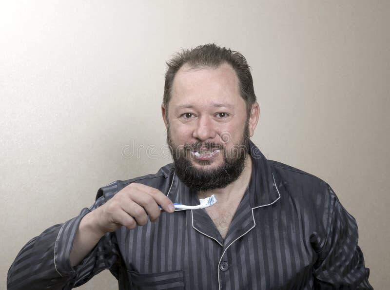 Hombre en los pijamas que cepillan sus dientes con un cepillo de dientes fotos de archivo libres de regalías