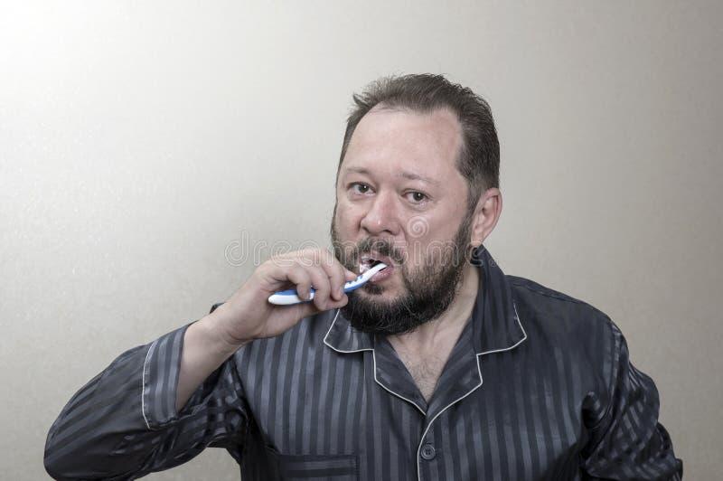 Hombre en los pijamas que cepillan sus dientes con un cepillo de dientes foto de archivo libre de regalías