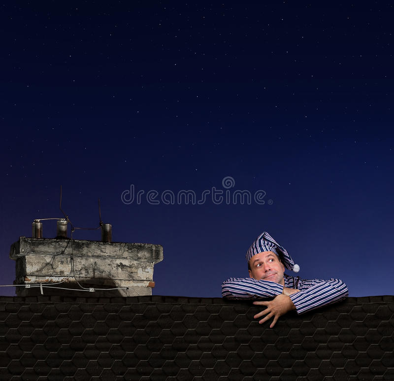 Hombre en los pijamas que suben en el tejado imagen de archivo