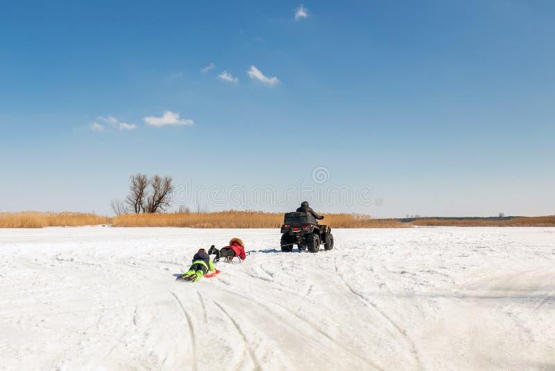 Hombre en los trineos que montan del quadbike de ATV con los niños a remolque en superficie congelada del lago en el invierno Dep foto de archivo