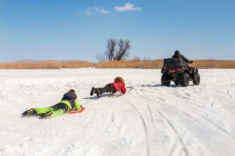 Hombre en los trineos que montan del quadbike de ATV con los niños a remolque en superficie congelada del lago en el invierno Dep fotos de archivo libres de regalías