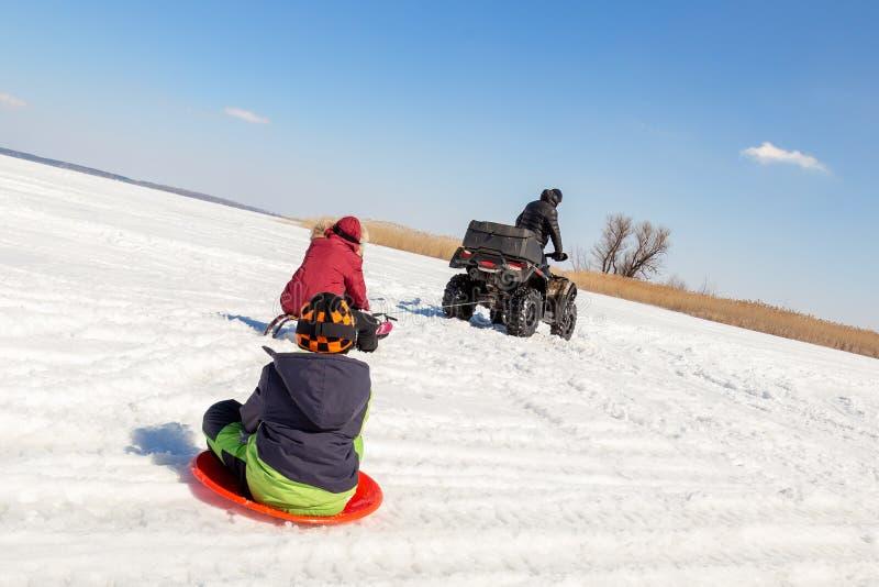 Hombre en los trineos que montan del quadbike de ATV con los niños a remolque en superficie congelada del lago en el invierno Dep imagen de archivo libre de regalías