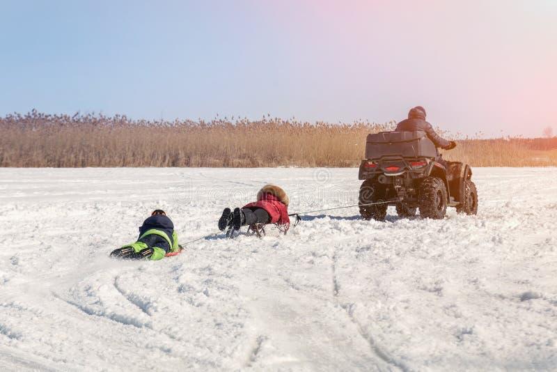 Hombre en los trineos que montan del quadbike de ATV con los niños a remolque en superficie congelada del lago en el invierno Dep foto de archivo libre de regalías